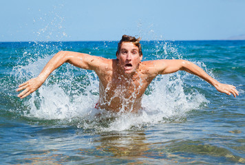 man swimming butterfly strokes in ocean