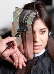 Close up of a hairdresser coloring woman's hair. Selective focus