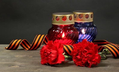Memory lantern with candles, red carnations and St. George