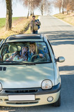 Exciting girls drive car taking hitch-hiker