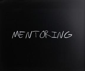 """Mentoring"" handwritten with white chalk on a blackboard"