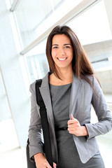 Smiling businesswoman in hall with briefcase