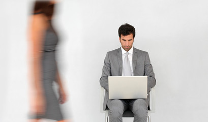 Businessman with laptop and woman passing by