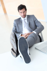 Businessman relaxing wih feet on desk