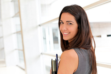 Young businesswoman in modern building holding files