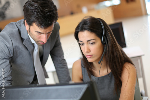 Sales representative with manager in front of desktop