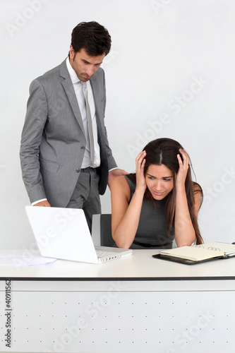 Businessman in office harassing young woman