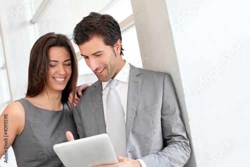 Business partners working in hall on electronic tablet