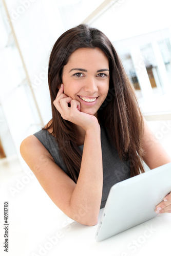 Portrait of smiling student using electronic tablet