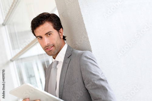 Businessman standing in hall with electronic tablet