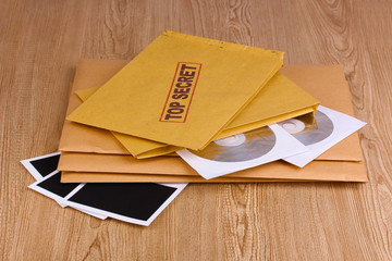 Envelopes with top secret stamp with photo papers and CD disks