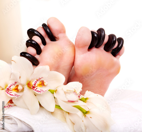 Woman receiving stone massage on feet.