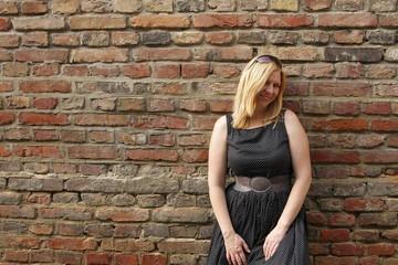 Blonde Frau lehnt an Ziegelmauer