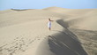 Woman in white dress running in the desert, slow motion