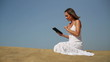 Young woman using tablet computer on the beach
