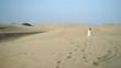 Woman in white dress walking in the desert