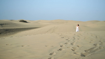Woman in white dress walking in the desert