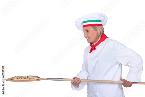 Italian chef putting a pizza in the oven