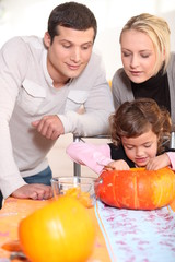 Little girl and parents carving pumpkin for Halloween