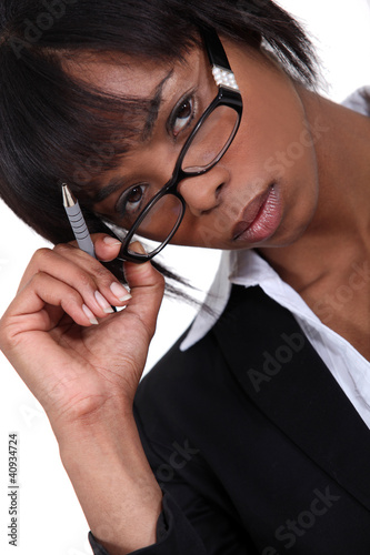 Businesswoman with pen lifting glasses frame