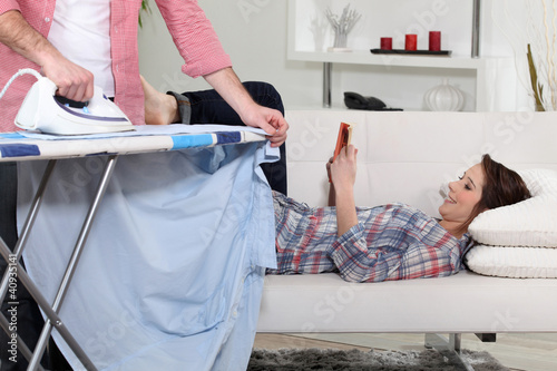 Woman reading while her boyfriend does housework