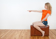 Young woman sitting on a suitcase and pointing direction