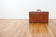 Retro leather suitcase on wooden floor
