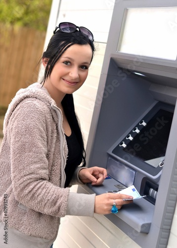 Beautiful woman using ATM Poster