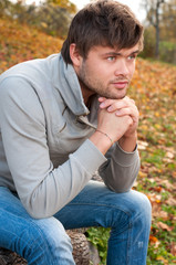 Outdoors portrait of happy young man sitting in autumn park