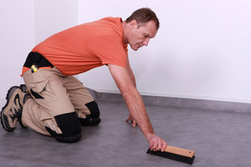 A man laying lino.