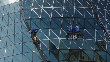 Finishing the modern building. Builders on the scaffoldings.