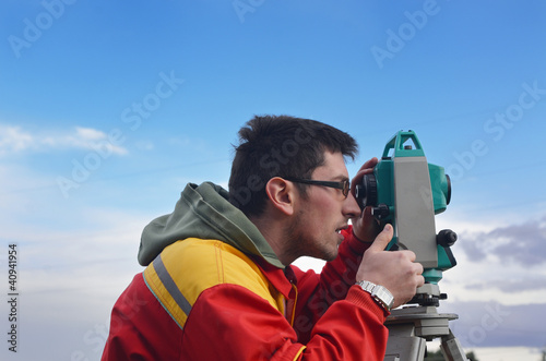 One surveyor worker working with theodolite transit equipment at
