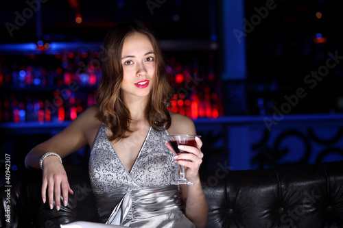 Young woman in night club with a drink