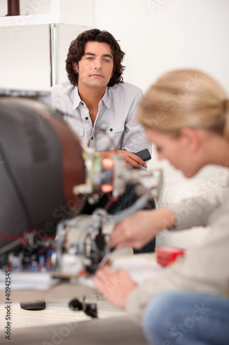 Man watching a woman repair a TV set