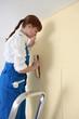 Woman smoothing wallpaper