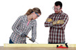 female carpenter at work with male workmate watching her
