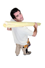 High-angle shot of a handyman carrying wooden planks