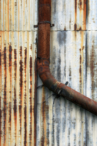Rusty Pipe on Corrugated Metal