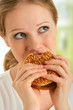 attractive young  woman eats unhealthy food, hamburger