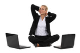 Blond businesswoman sat cross-legged with two laptops