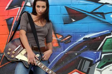 Female guitarist stood by graffiti