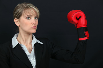 Businesswoman wearing a boxing glove