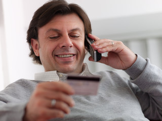 adult man shopping from home with telephone and credit card