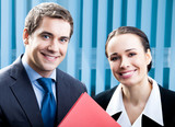 Two happy businesspeople with folder at office