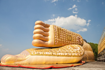 Gold Buddha feet with blue sky