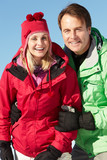Couple Standing In Snow Wearing Warm Clothes On Ski Holiday In M