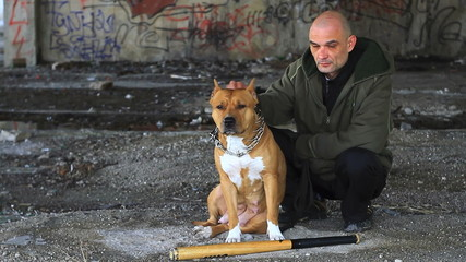 Criminal posing with bat and pit bull in front of graffiti