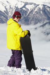 Teenage Snowboarder Admiring Mountain View Whilst On Ski Holiday