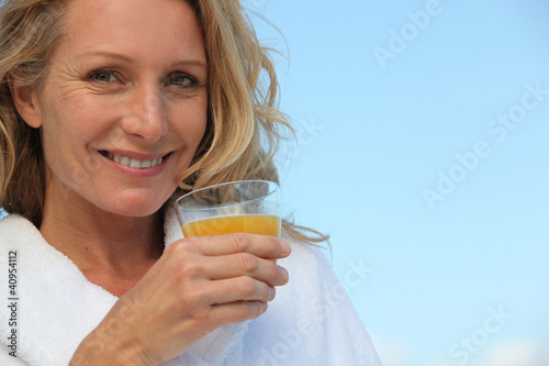 Blond woman outdoors drinking orange juice