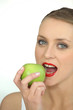 Woman biting into green apple